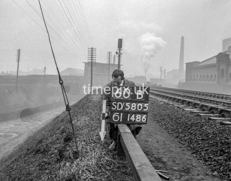 SD580560B, Man marking Ordnance Survey minor control revision point with an arrow in 1950s