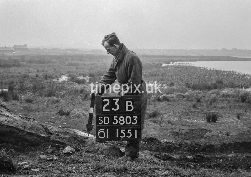 SD580323B, Man marking Ordnance Survey minor control revision point with an arrow in 1950s