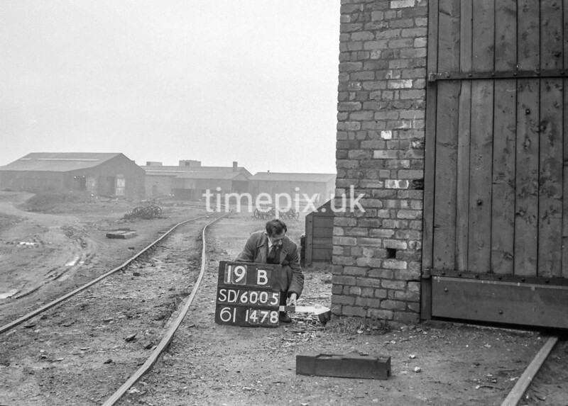 SD600519B, Man marking Ordnance Survey minor control revision point with an arrow in 1950s