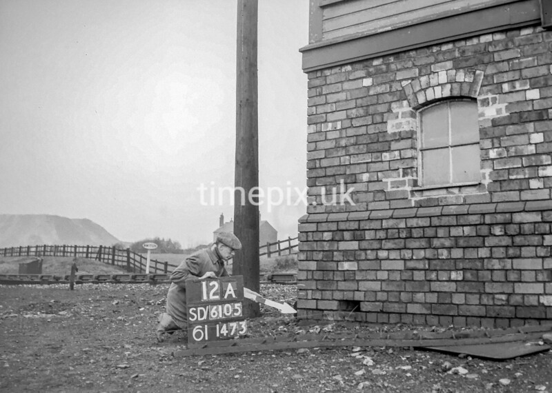 SD610512A, Man marking Ordnance Survey minor control revision point with an arrow in 1950s