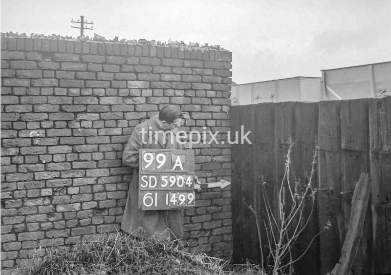 SD590499A, Man marking Ordnance Survey minor control revision point with an arrow in 1950s