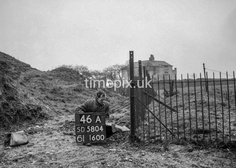 SD580446A, Man marking Ordnance Survey minor control revision point with an arrow in 1950s