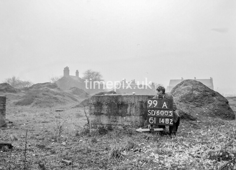 SD600599A, Man marking Ordnance Survey minor control revision point with an arrow in 1950s