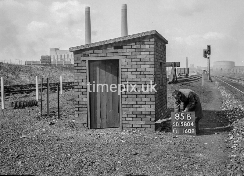 SD580485B, Man marking Ordnance Survey minor control revision point with an arrow in 1950s
