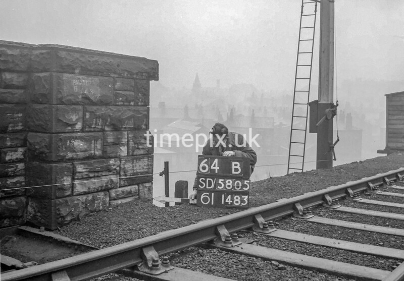 SD580564B, Man marking Ordnance Survey minor control revision point with an arrow in 1950s