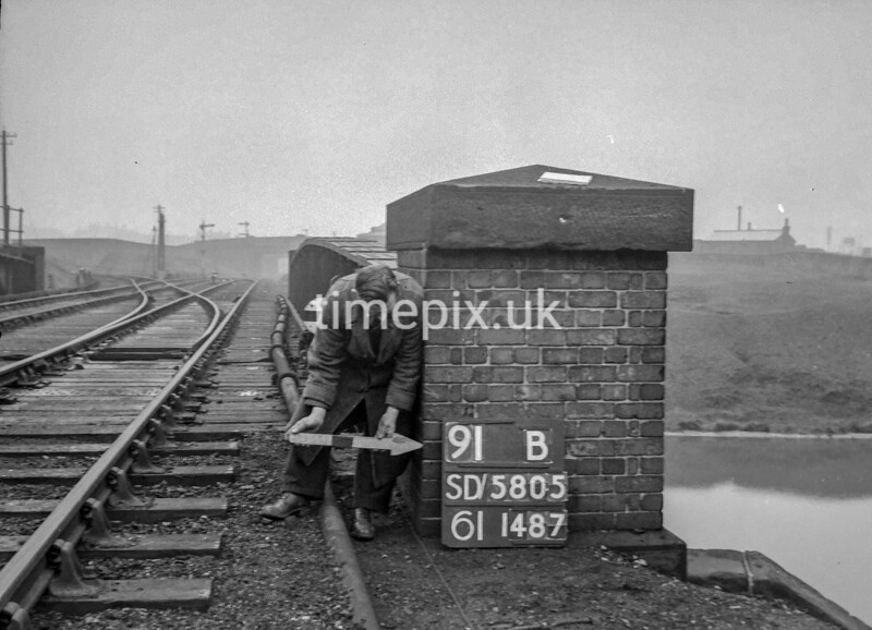 SD580591B, Man marking Ordnance Survey minor control revision point with an arrow in 1950s