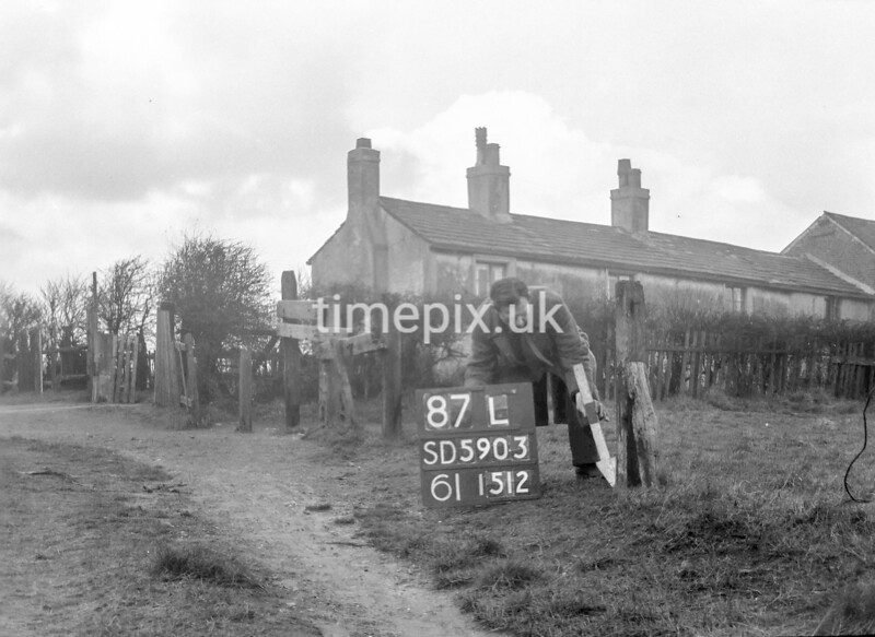 SD590387L, Man marking Ordnance Survey minor control revision point with an arrow in 1950s
