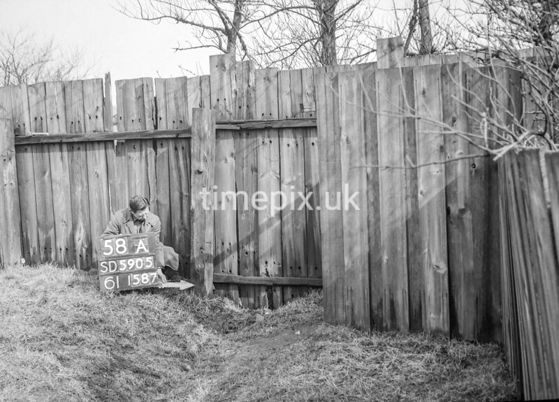 SD590558A, Man marking Ordnance Survey minor control revision point with an arrow in 1950s