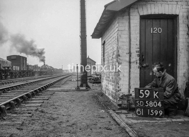 SD580459K, Man marking Ordnance Survey minor control revision point with an arrow in 1950s