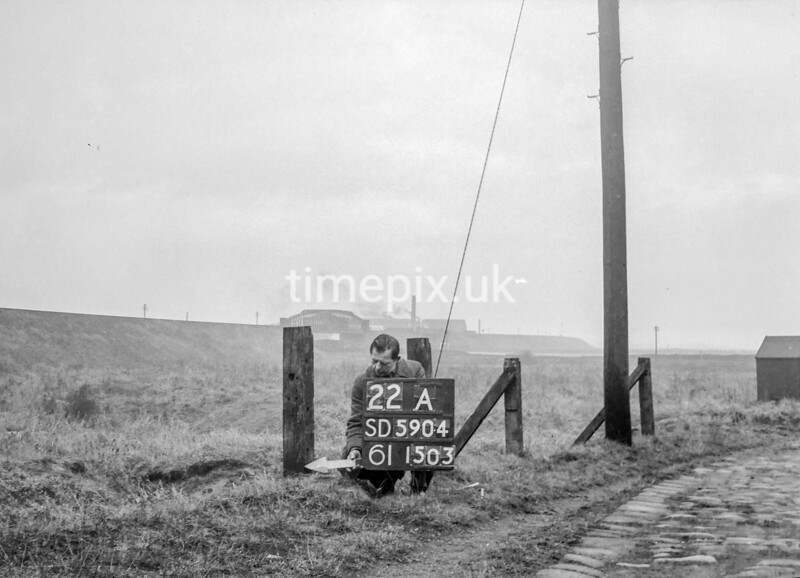SD590422A, Man marking Ordnance Survey minor control revision point with an arrow in 1950s
