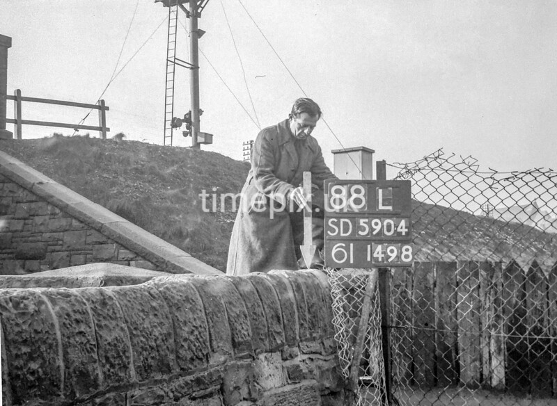 SD590488L, Man marking Ordnance Survey minor control revision point with an arrow in 1950s