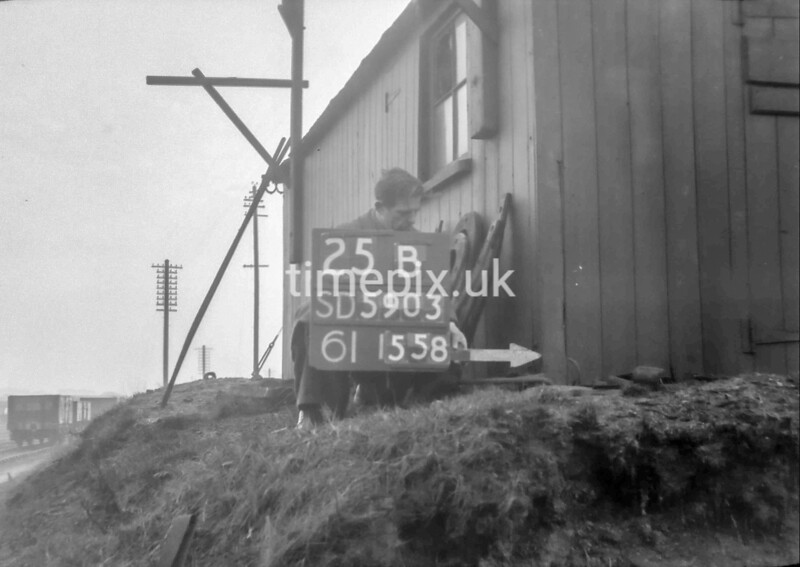 SD590325B, Man marking Ordnance Survey minor control revision point with an arrow in 1950s