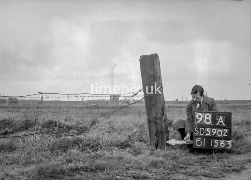 SD590298A, Man marking Ordnance Survey minor control revision point with an arrow in 1950s