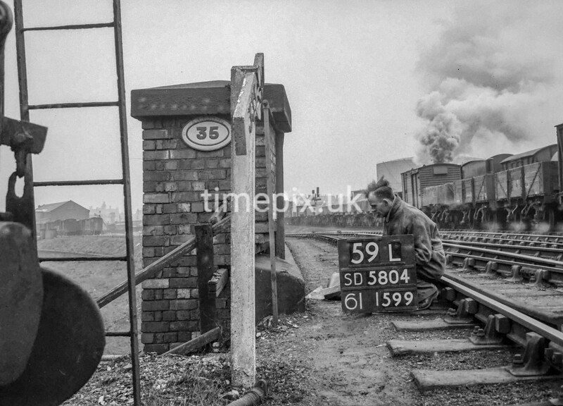 SD580459L, Man marking Ordnance Survey minor control revision point with an arrow in 1950s