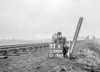 SD590433A, Man marking Ordnance Survey minor control revision point with an arrow in 1950s
