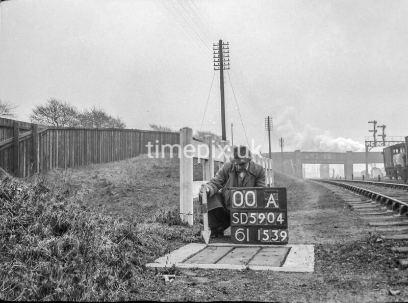 SD590400A, Man marking Ordnance Survey minor control revision point with an arrow in 1950s