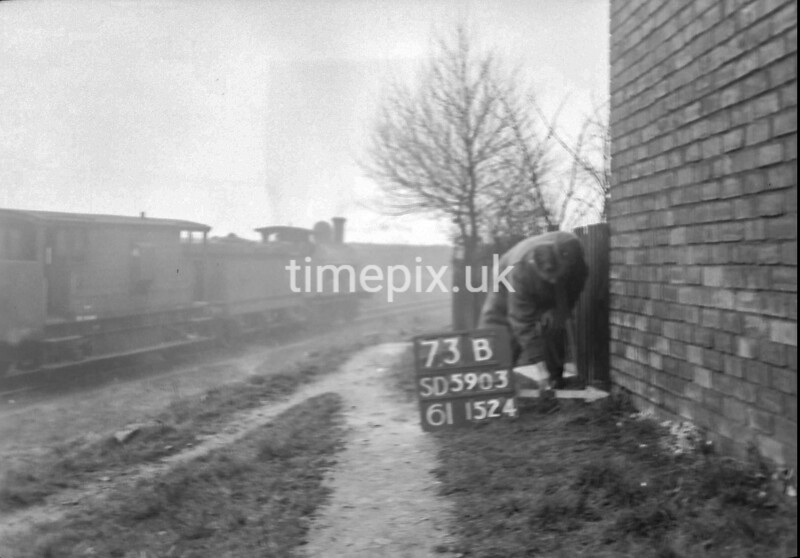SD590373B, Man marking Ordnance Survey minor control revision point with an arrow in 1950s