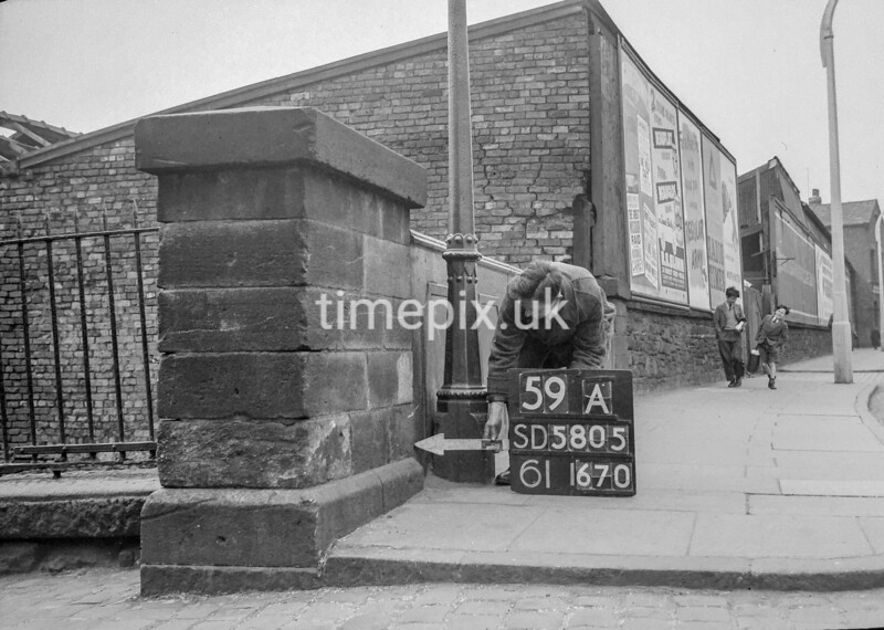 SD580559A, Man marking Ordnance Survey minor control revision point with an arrow in 1950s
