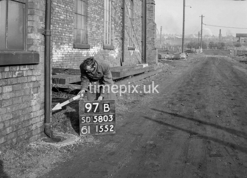 SD580397B, Man marking Ordnance Survey minor control revision point with an arrow in 1950s
