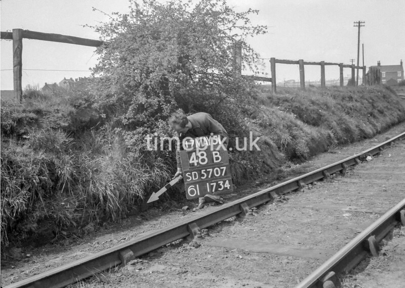 SD570748B, Man marking Ordnance Survey minor control revision point with an arrow in 1950s