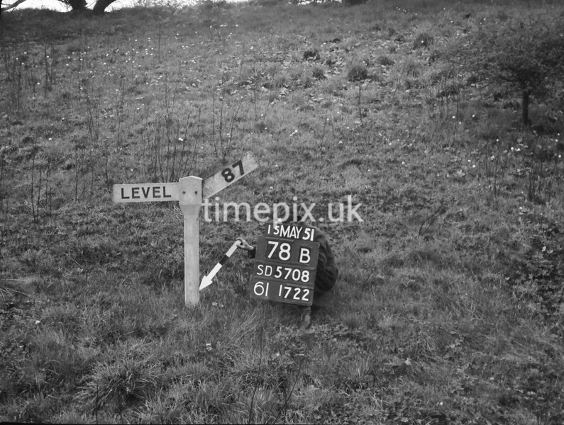 SD570878B, Man marking Ordnance Survey minor control revision point with an arrow in 1950s