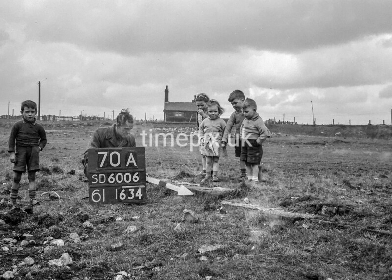 SD600670A, Man marking Ordnance Survey minor control revision point with an arrow in 1950s