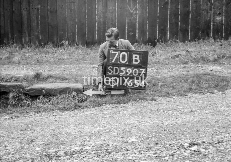 SD590770B, Man marking Ordnance Survey minor control revision point with an arrow in 1950s