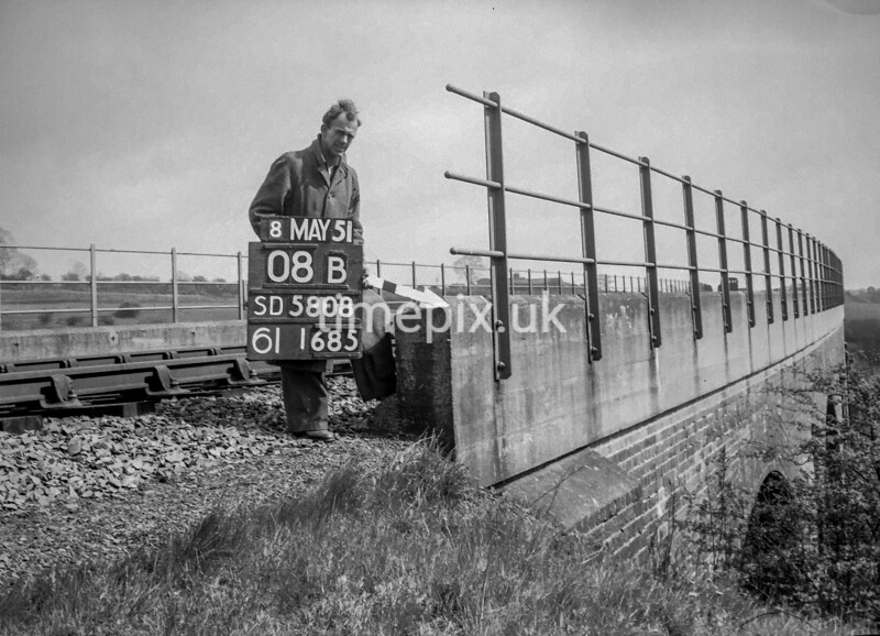 SD580808B, Man marking Ordnance Survey minor control revision point with an arrow in 1950s