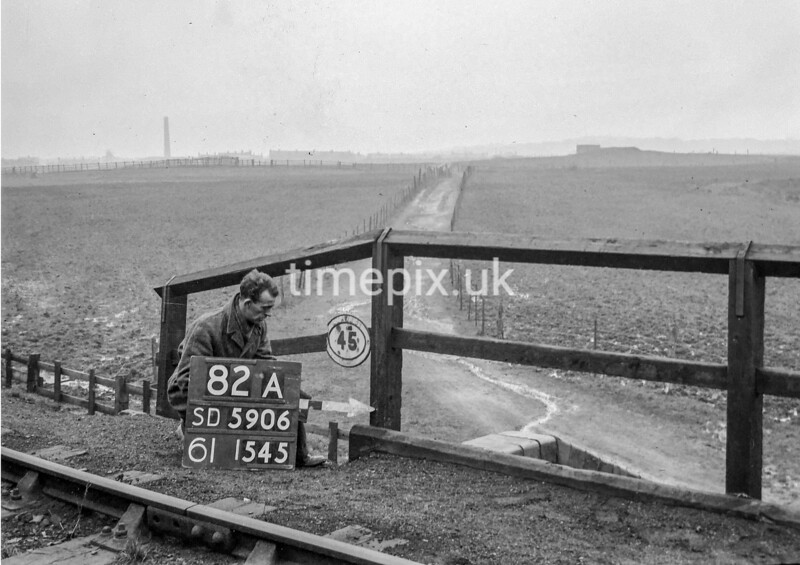 SD590682A, Man marking Ordnance Survey minor control revision point with an arrow in 1950s