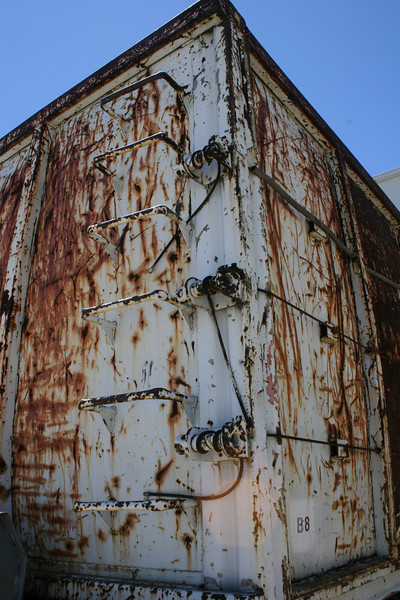 dented, rusty, and beautiful. old storage container sitting in the back parking lot of a shipping company.