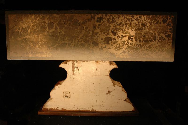 antique bell holder on dark wood base.