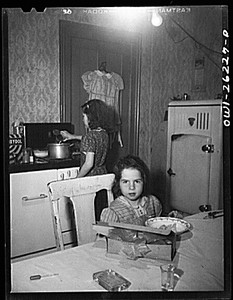 Beverly Ann Grimm, eleven, serving an omelette for Saturday lunch for her sisters and herself, while Pasty looks on. Their mother, a twenty-six year old widow, is a crane operator at Pratt and Letchworth
