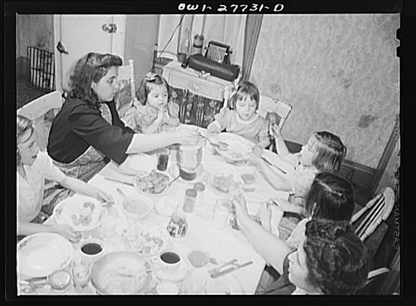 The Grimm family eating Sunday dinner. Mrs. Grimm, a twenty-six year old widow, is a crane operator at Pratt and Letchworth.