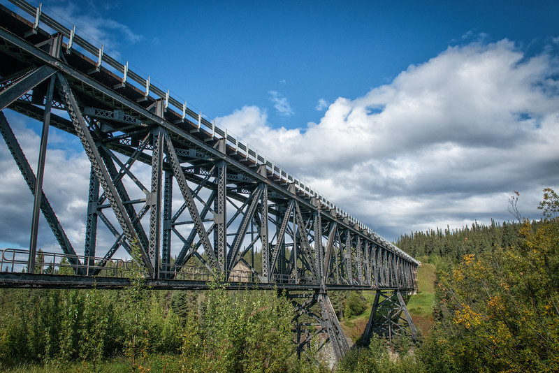 The Kuskulana Bridge spans a length of 600 feet and is the only railroad bridge in the area constructed of steel girders that span the canyon rather than timber pilings driven into a stream bed.