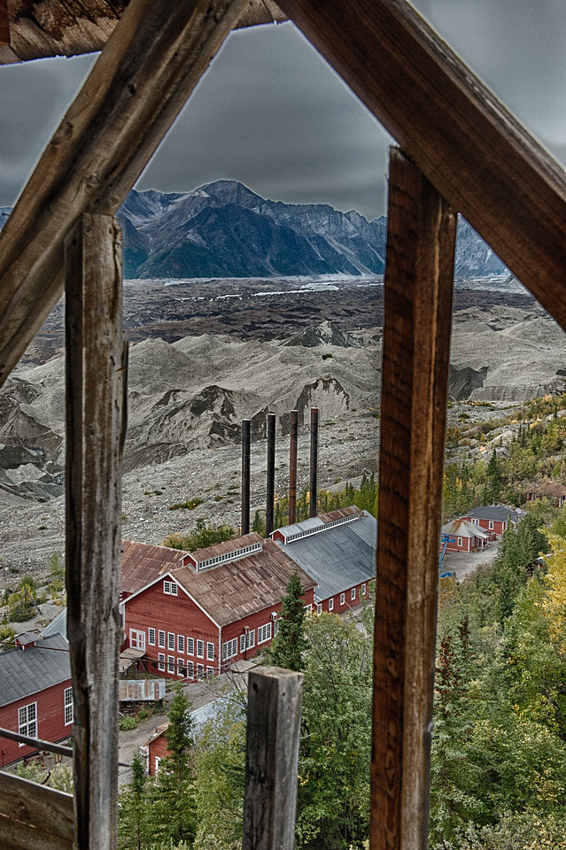 Through beams of the mill, a nicely framed view of the power plant and Kennicott Glacier. Pale processing with a bit of saturation restored for the reds.