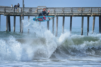 A surfer catching air on a wave near the Pismo Pier in Pismo California along highway 1