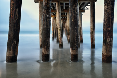 Waves rolling in at low tide under the iconic Pismo Pier in Pismo California along highway 1