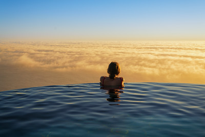 A young lady enjoys a view of the Big Sur Coastline from a swimming pool high above the ocean, Big Sur coastline California