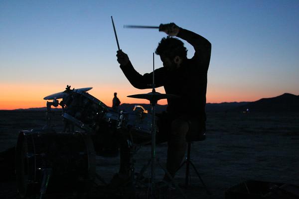 Obhi rocks drums at sunrise in deep playa.