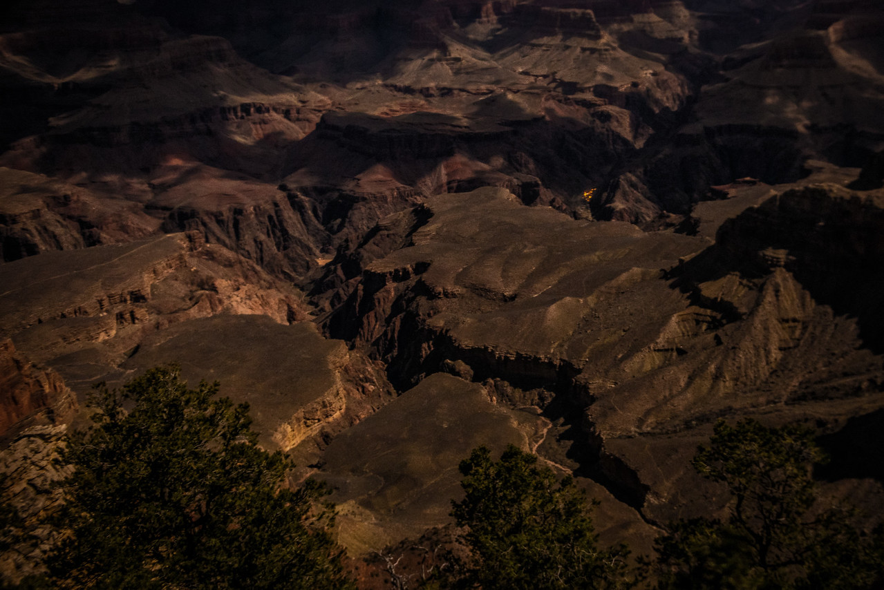 The lights of Phantom Ranch shine through a moon lit night. View from Mather Point.