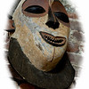 "December 20, 2009 - ""A Smile?""<br /> <br /> This mask and yesterdays ""Unlatched"" photo were captured at an African Arts & Crafts Gallery in Galveston.  I have created a gallery with the masks that I photographed along with some additional post processing at<br /> <br />  <a href=""http://dakotacowboy.smugmug.com/Photography/Masks/10670791_u87G9/1/744755306_s6gQb"">http://dakotacowboy.smugmug.com/Photography/Masks/10670791_u87G9/1/744755306_s6gQb</a><br /> <br /> The door in yesterdays shot was from Africa and for sale.  I did not notice the price.<br /> <br /> None of the mask photos stood out as one that I liked best, so this one is the first shot that I took in the store.  Because the masks were close together, I did some white vignetting to cover their immediate surroundings."