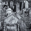 "December 9, 2009 - ""Old Cemetery"" <br /> <br /> This image has been processed from a Fujifilm Color negative that I shot in the late 90's in Prague in the old Jewish Cemetery.  I have looked at the scan several times with different processing ideas, but never have been satisfied enough to present it.  I recently saw a wide crop of something else that gave me the idea to present the image this way.  Suggest viewing enlarged.<br /> <br /> From Wikipedia, the free encyclopedia - Dec. 8, 2010<br /> ""The Old Jewish Cemetery lies in the Josefov, the Jewish Quarter of Prague in the Czech Republic. It was in use from the early 15th century (the oldest preserved tombstone, the one of Avigdor Kara, dates back to 1439) until 1787. Its ancestor was a cemetery called ""The Jewish Garden"", which was found in archaeological excavations under the Vladislavova street, New Town.<br /> The numbers of grave stones and numbers of people buried there are uncertain, because there are layers of tombs. However, it has been estimated that there are approximately 12,000 tombstones presently visible, and there may be as many as 100,000 burials in all. The most important personalities buried in the Old Jewish Cemetery are Yehuda ben Bezalel known as the Maharal Rabbi Löw (d. 1609), Mordechai Maisel (d. 1601), David Gans (d. 1613) and David Oppenheim (d. 1736).<br /> <br /> ..........      According to halakhah, Jews must not destroy Jewish graves and in particular it is not allowed to remove the tombstone. This meant that when the cemetery ran out of space and purchasing extra land was impossible, more layers of soil were placed on the existing graves, the old tombstones taken out and placed upon the new layer of soil. This explains why the tombstones in the cemetery are placed so closely to each other. This resulted in the cemetery having 12 layers of graves."""