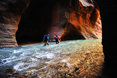 "Hikers moving through the Virgin River along the iconic walls of ""The Narrows"" in Zion National Park Utah"