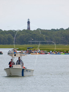 The Coast Guard keeps an eye on the current, waiting for it to be at it's slowest to allow for the safest passage across the channel.  Assateague Island Lighthouse in the background.