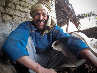 Desraj, a farmer at Niramayam Farm near Dharamshala, India gathers up cow dung compost.