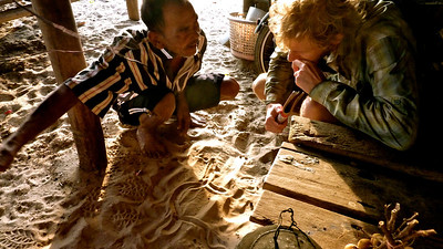 A Thai fisherman draws a map in the sand for Adam. Thailand 2011
