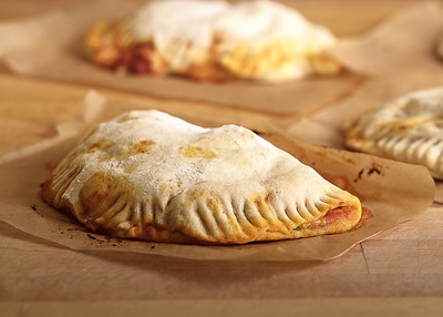 Freshly Baked Calzone On Sheets Of Parchment Paper