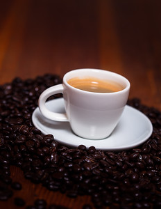 Cup Of Espresso And Beans On A Wooden Table