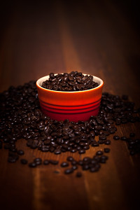 A Bowl Of Coffee Beans On A Wooden Table