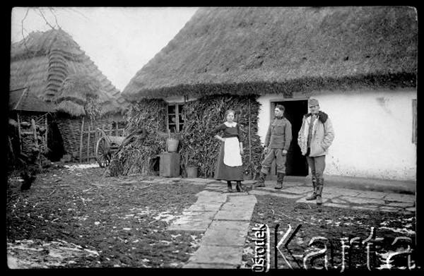 1914-1918, brak miejsca (prawdopodobnie Żeżawa, powiat Zaleszczyki)<br /> <br /> Na pdwórku przed chałupą stoi młoda dziewczyna i dwaj żołnierze armii austriackiej.<br /> <br /> Fot. NN, zbiory Ośrodka KARTA, udostępnił Mariusz Hermanowicz.